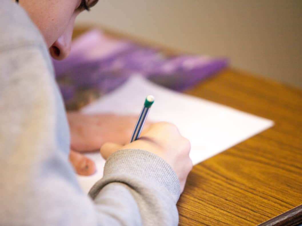 Student writing at desk